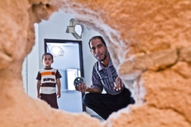 A resident of Ajdabiya holds up a fragment of the rocket that put three different holes in his house.